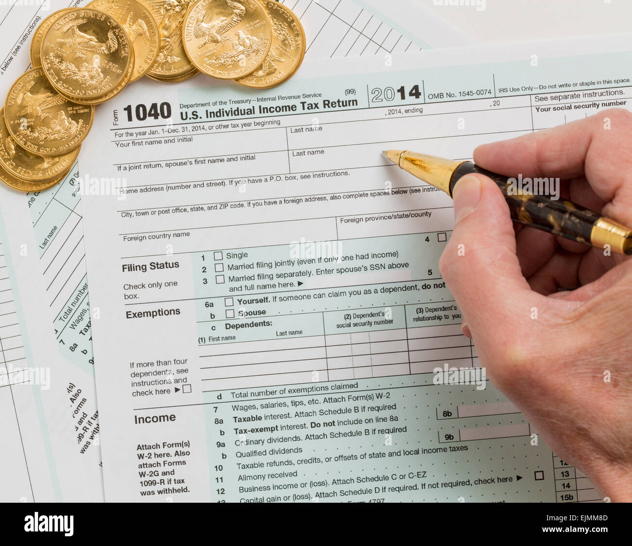 Caucasian hand with pen and solid gold eagle coins on USA tax form 1040 for year 2014 illustrating payment of taxes - Stock Image