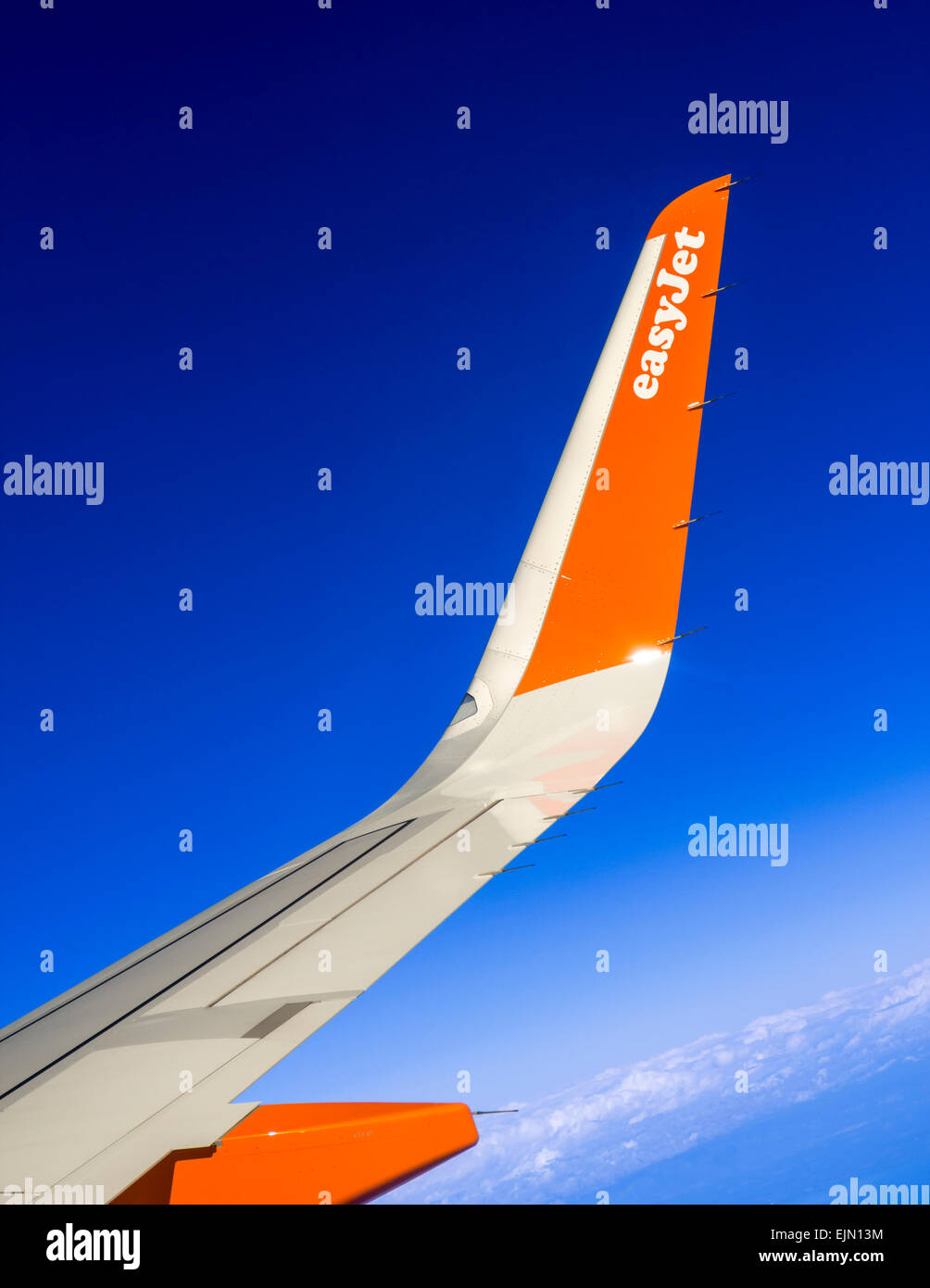 Wing of an Easyjet airplane in flight. - Stock Image