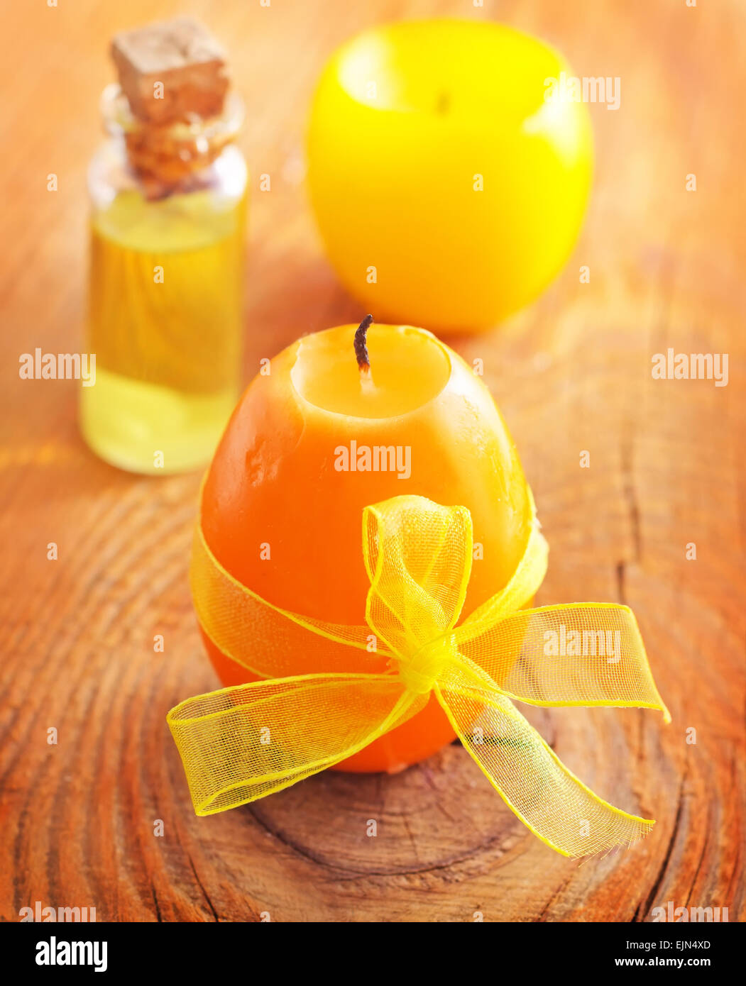 Aroma oil in glass bottl and candle on the wooden board - Stock Image