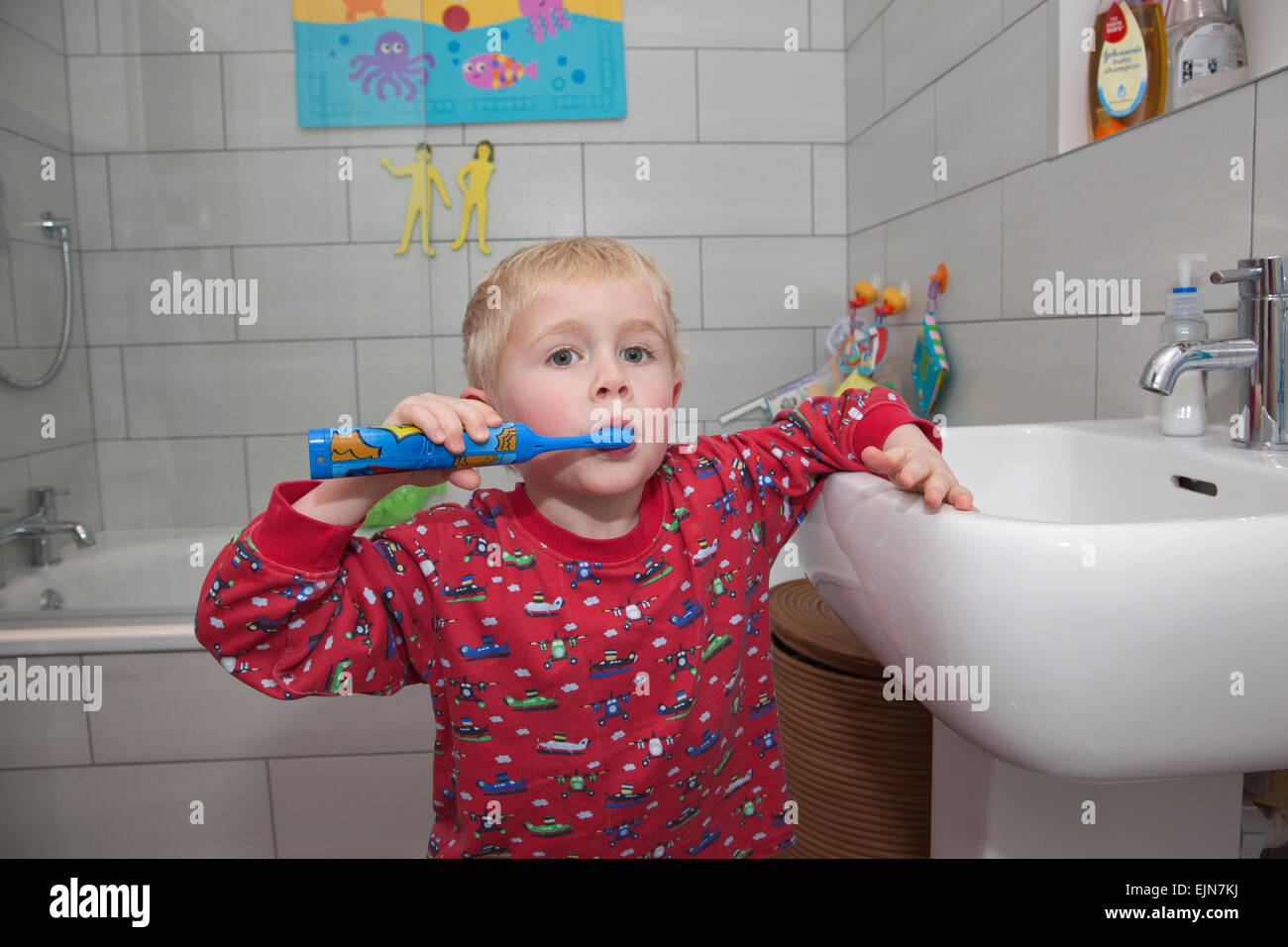 Four year old boy brushing his teeth with an electric toothbrush in the bathroom before bedtime, UK - Stock Image