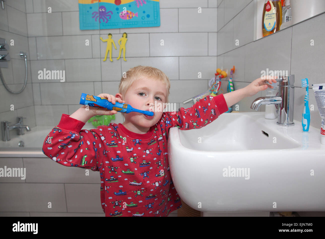 Four year old boy brushing his teeth with an electric toothbrush in the bathroom before bedtime, UK Stock Photo