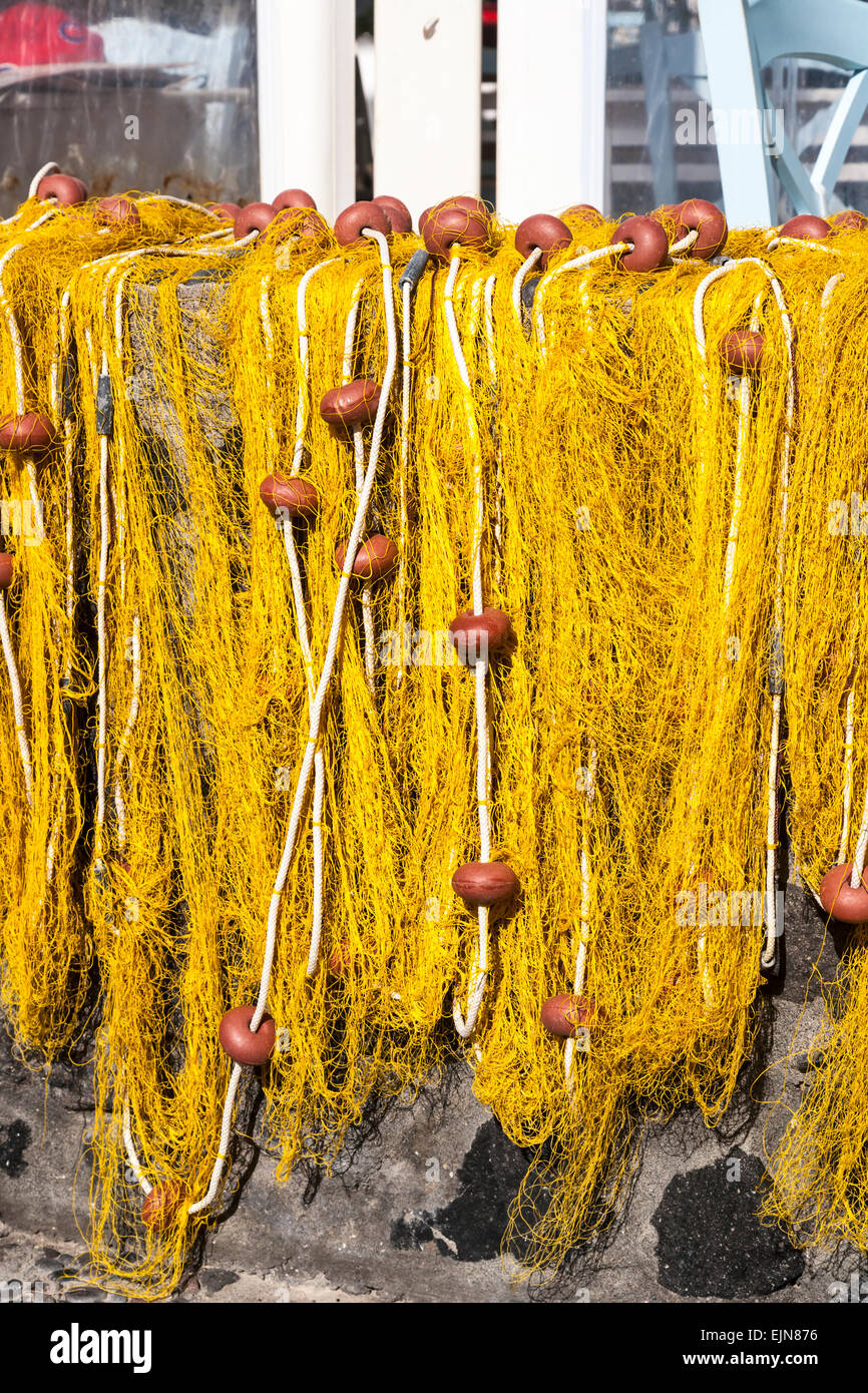 A Yellow fishing net draped over a wall, Santorini (Thera), Greece. - Stock Image