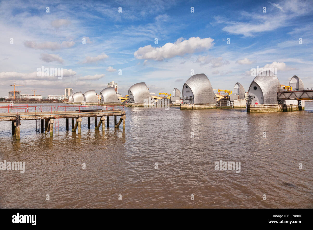 Thames Barrier, London, England, and an old jetty. - Stock Image