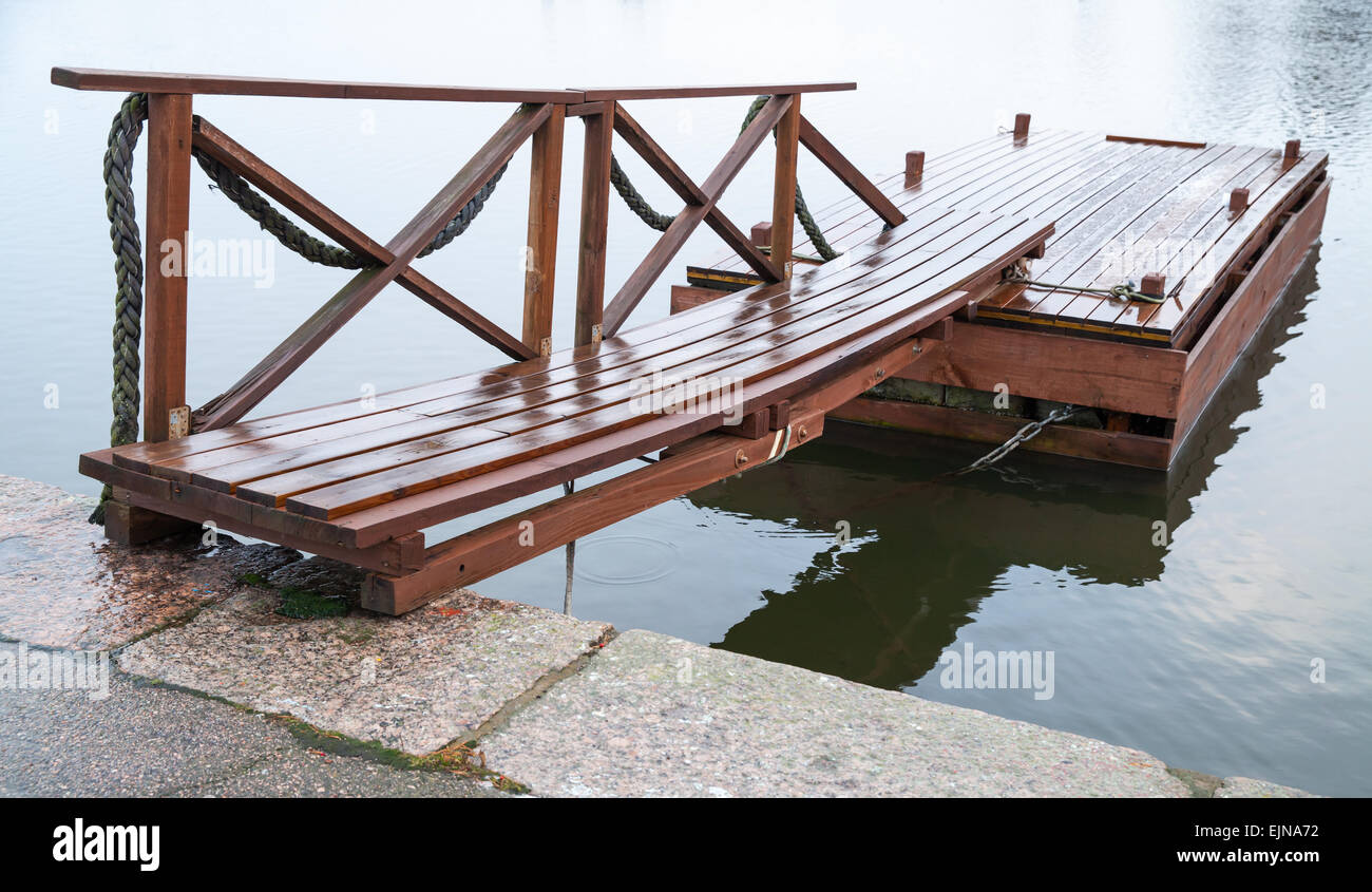 Shining wet wooden floating pier in still lake water, Finland - Stock Image
