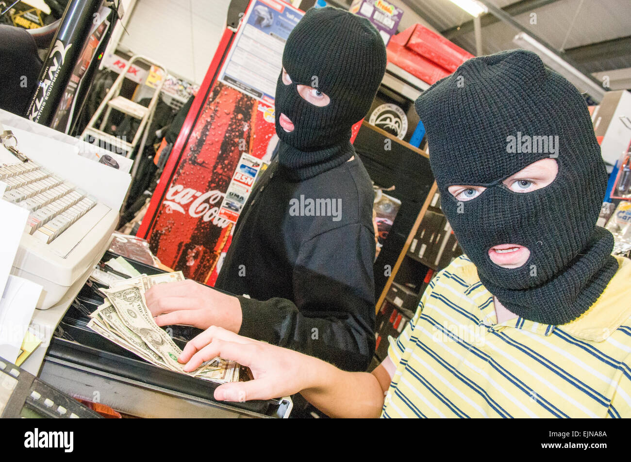 Two teenagers wear balaclavas while they steal money from the till of a shop. - Stock Image
