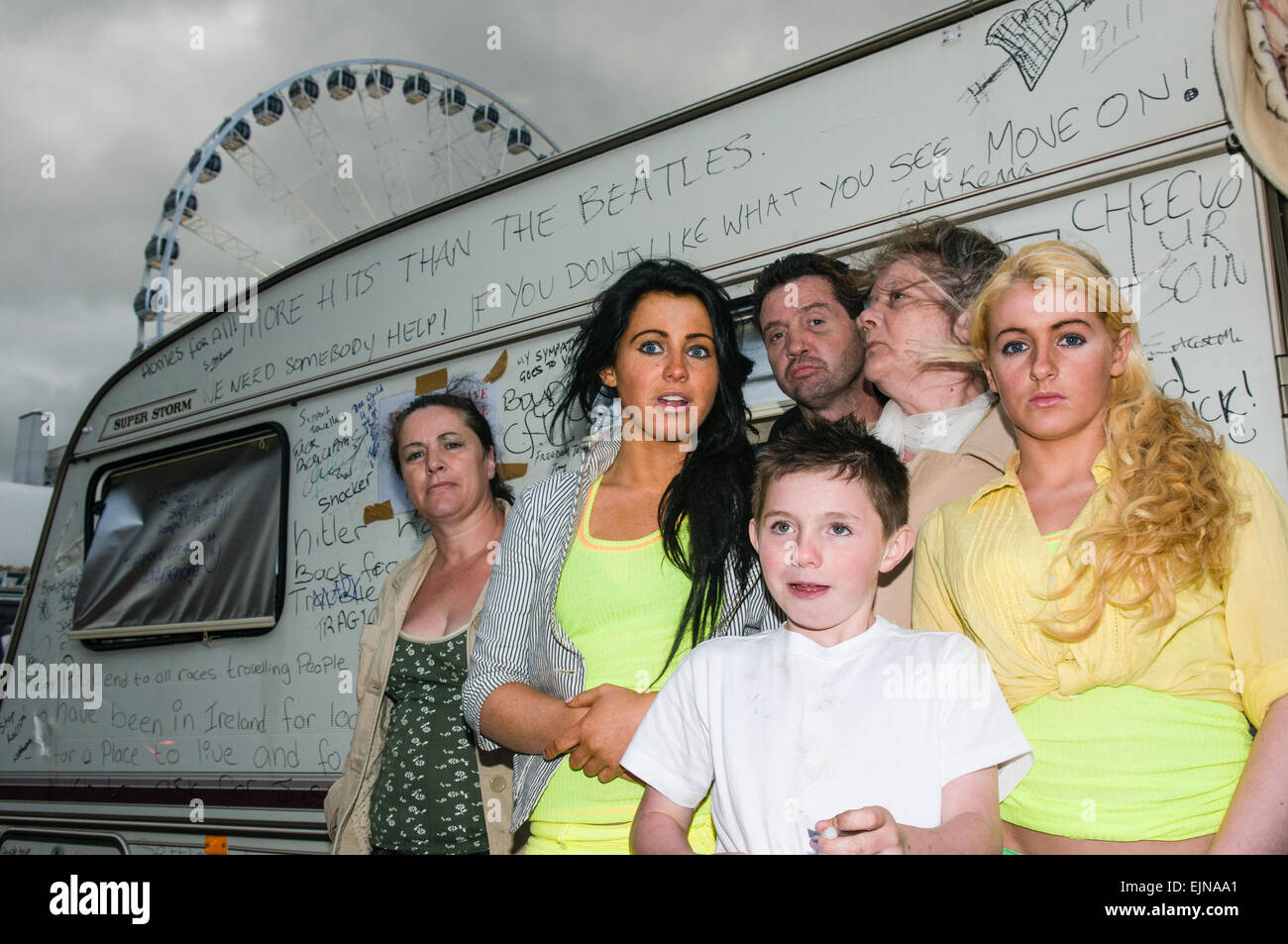 A gypsy traveller family stand outside their caravan, which has been written on with messages of support for their Stock Photo