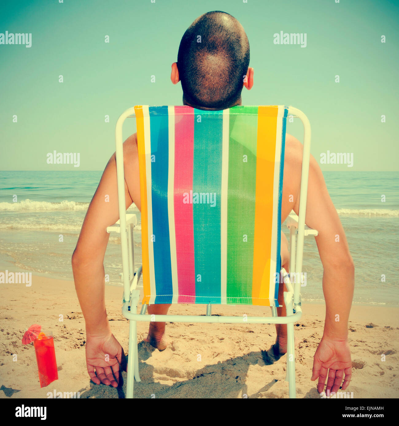 picture of a man sunbathing on a deckchair on the beach with a cocktail, with a retro effect - Stock Image