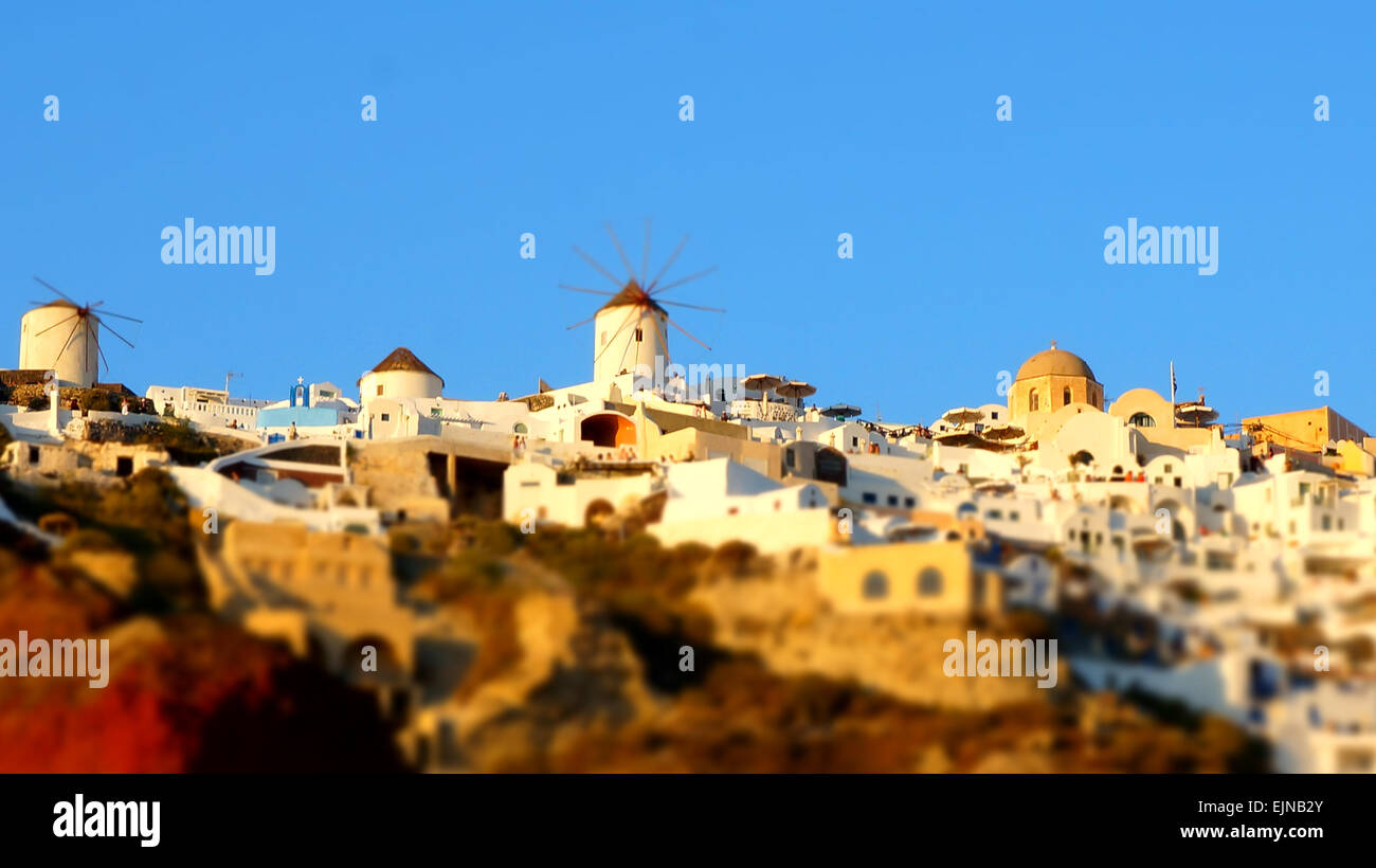 Golden sunset on the cliff house in Santorini, Greece. - Stock Image