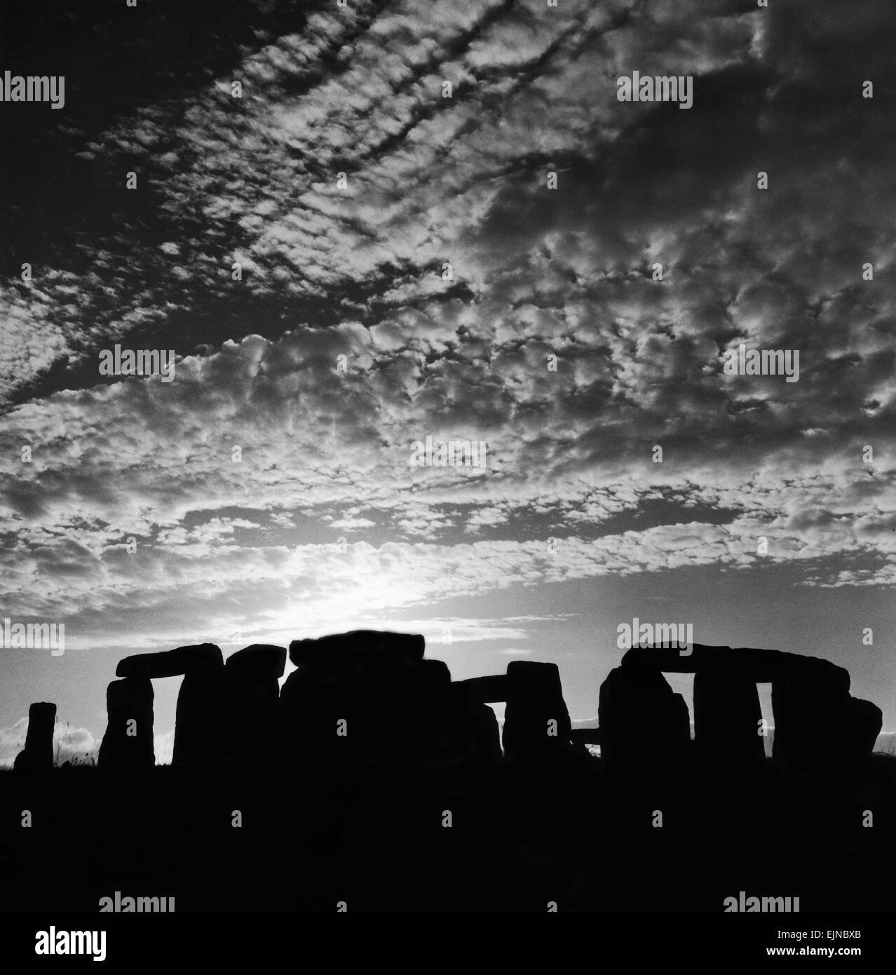 Sunset over Stonehenge in Wiltshire Britain Sunset Silhouette Clouds Druids Country Scene - Stock Image