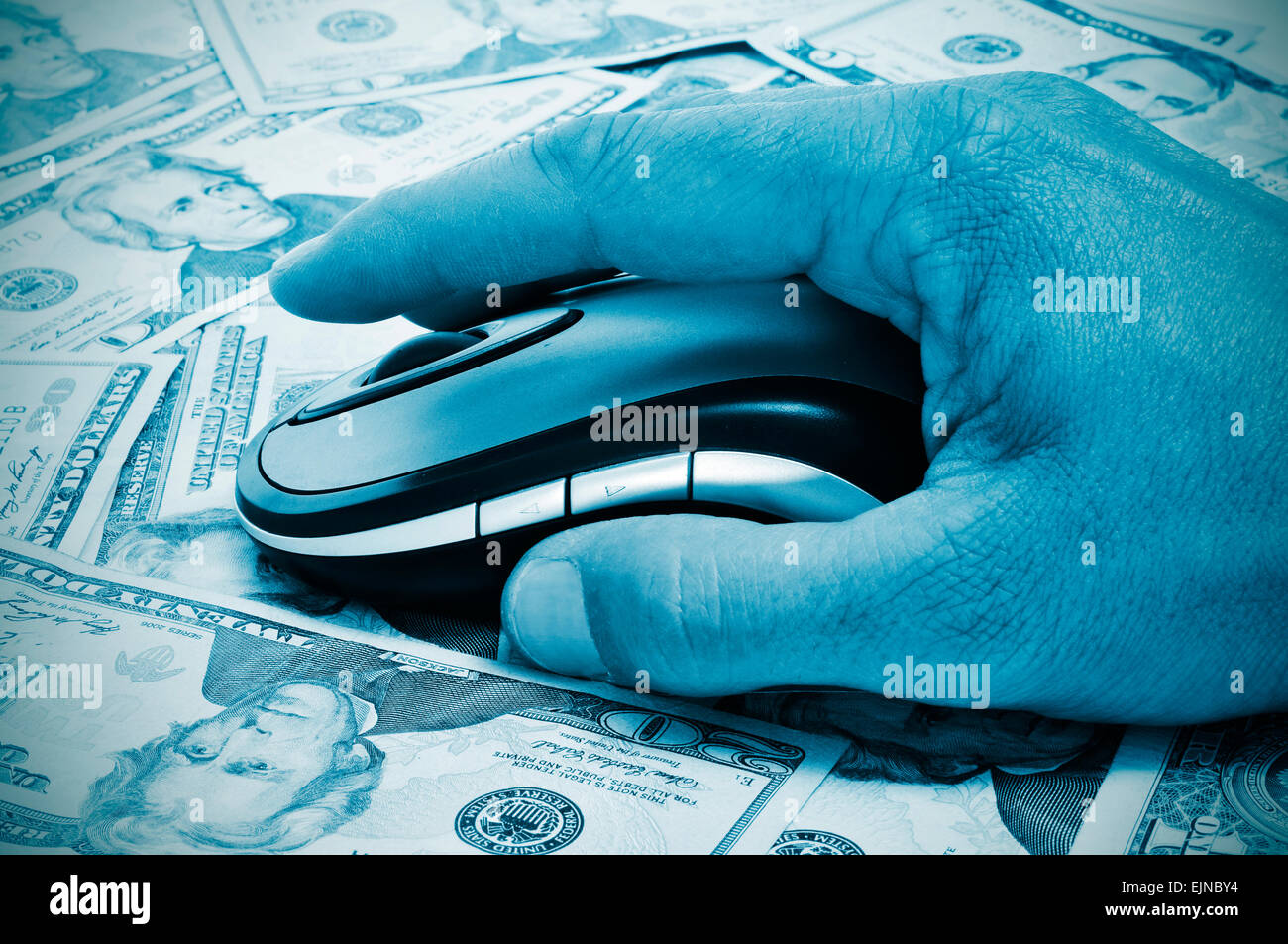 a hand man using a computer mouse on a background full of dollar banknotes, depicting the e-commerce concept or - Stock Image