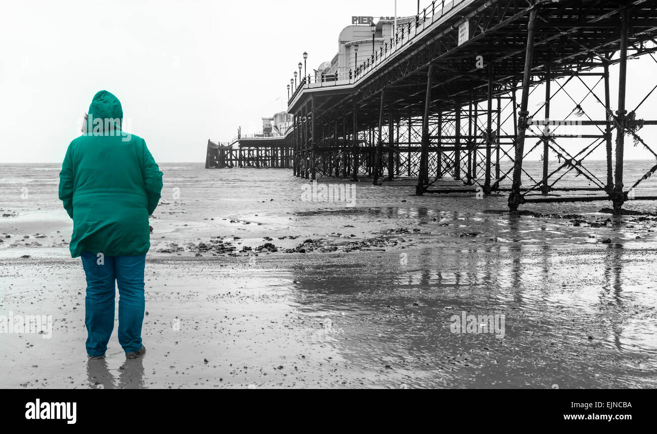 Mixed colour/Black and white image of a woman standing on a beach looking out to sea on a cold day. Selective colour. - Stock Image