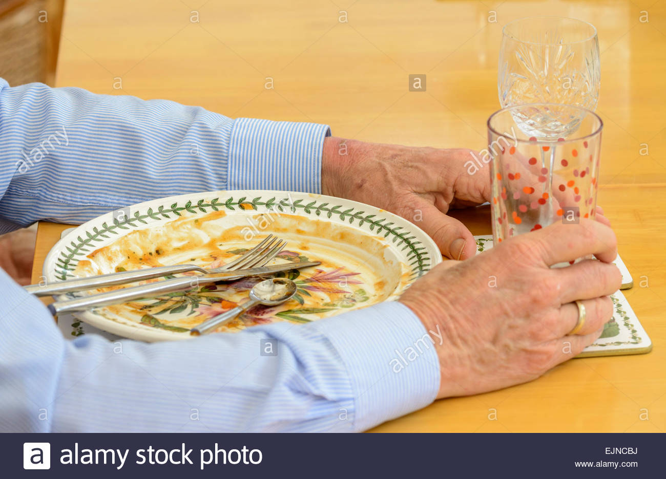 Man sitting with an empty dinner plate, knife, fork and glasses, after finishing a meal. - Stock Image
