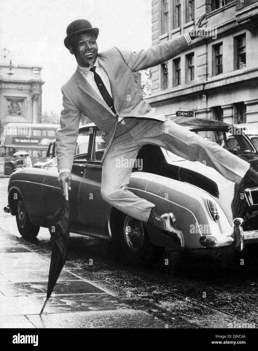Boxer Sugar Ray Robinson doing an impression of Sammy Davis Junior dressed in a city bowler hat and umbrella, in - Stock Image