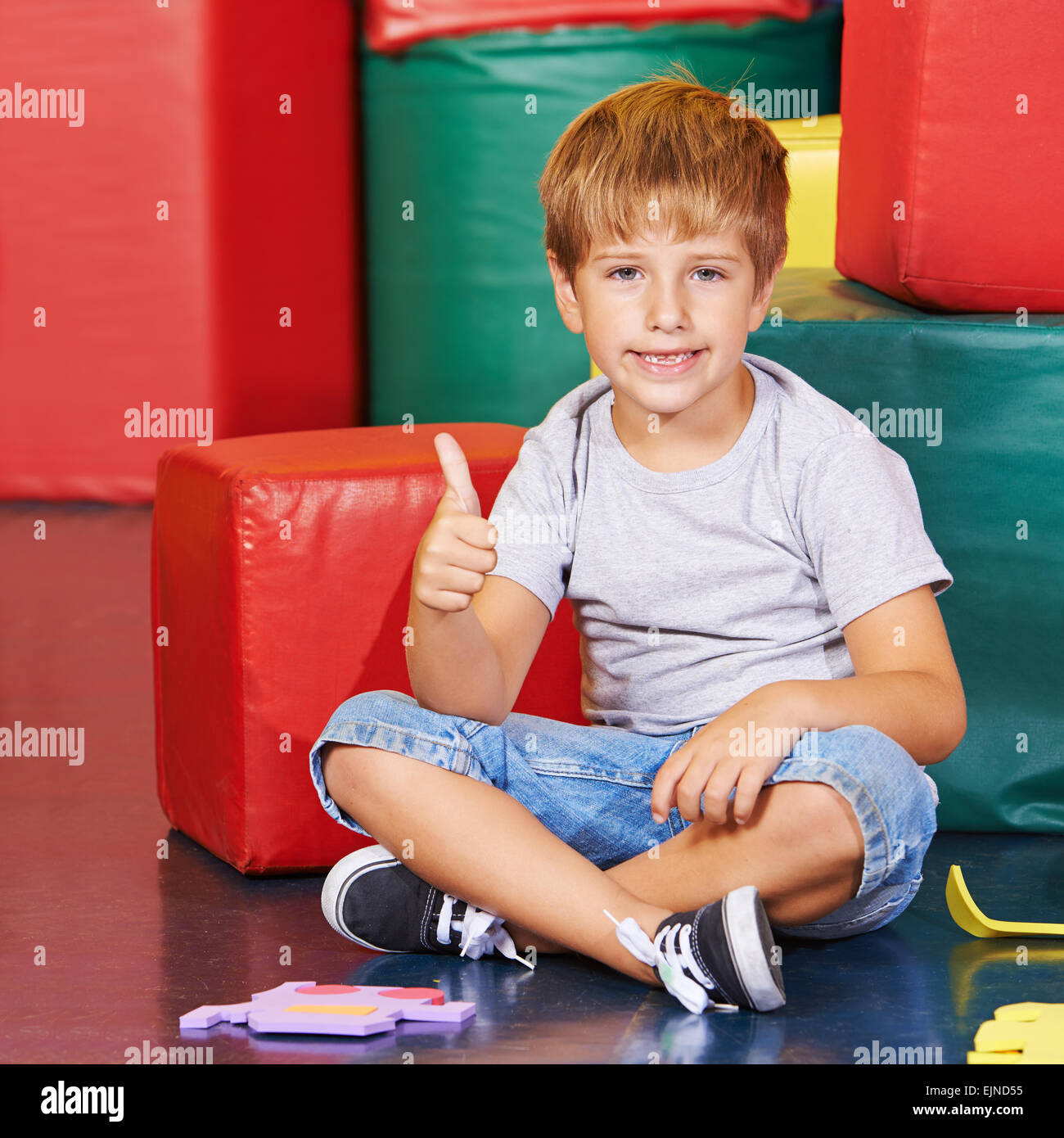 Happy boy holding his thumbs up in a kindergarten - Stock Image
