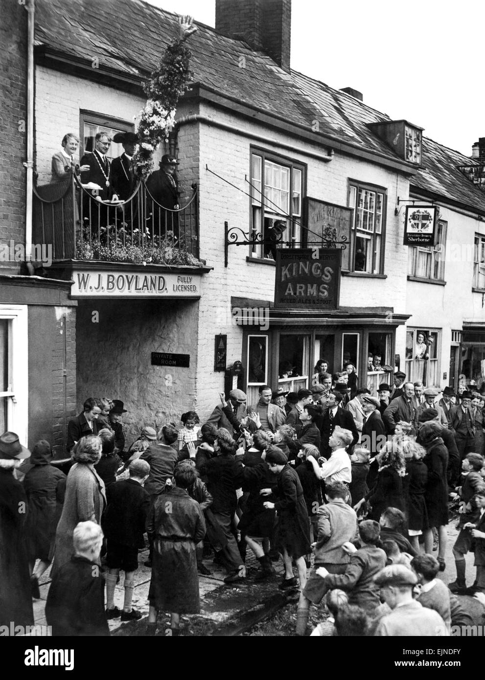 Throwing hot pennies to children at Honiton Fair Devon. The Hot Pennies ceremony takes place annually on the first - Stock Image