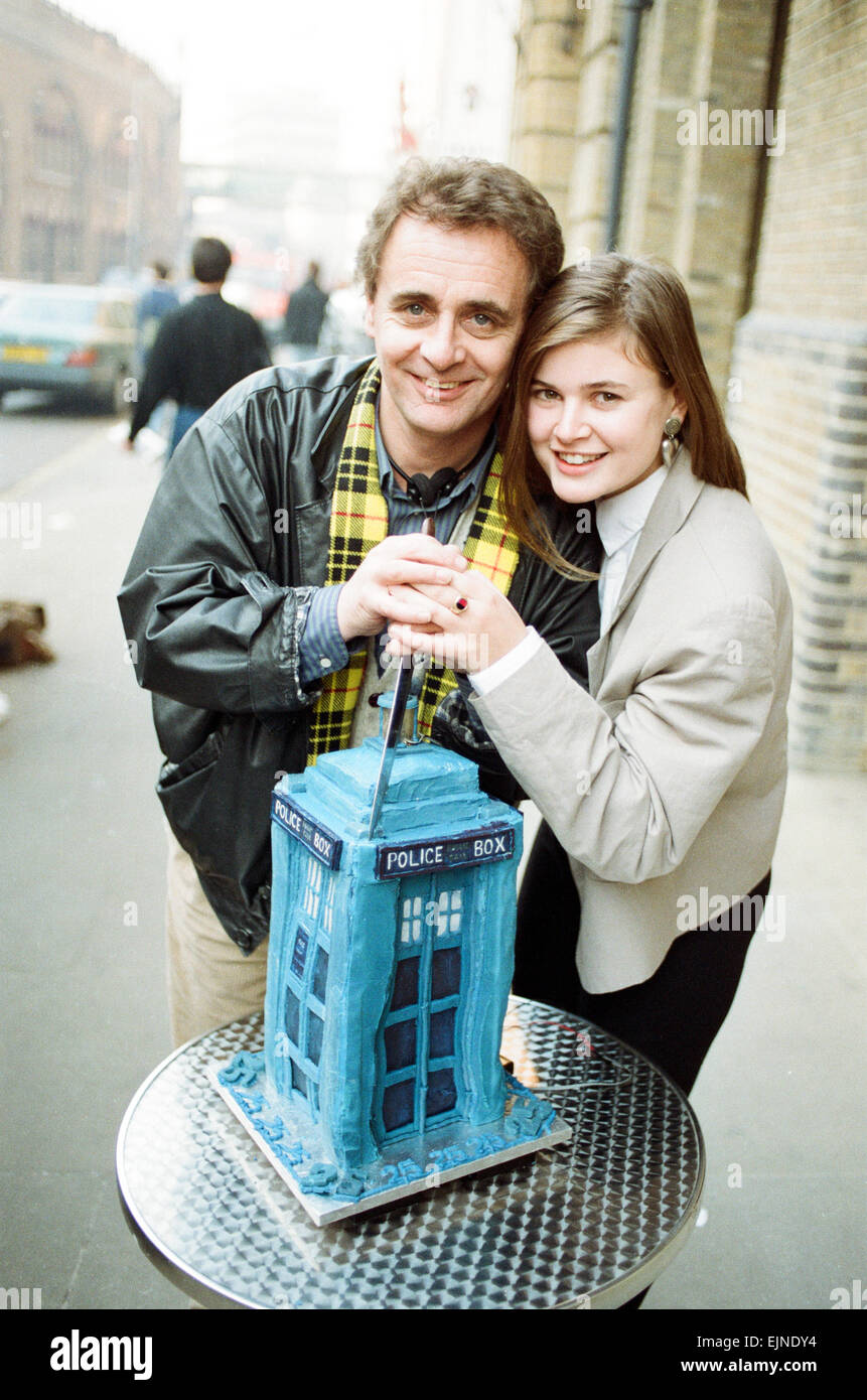 Dr Who, Sylvester McCoy with his assistant Ace alias Sophie Aldred cutting a cake in the shape of the tardis during - Stock Image