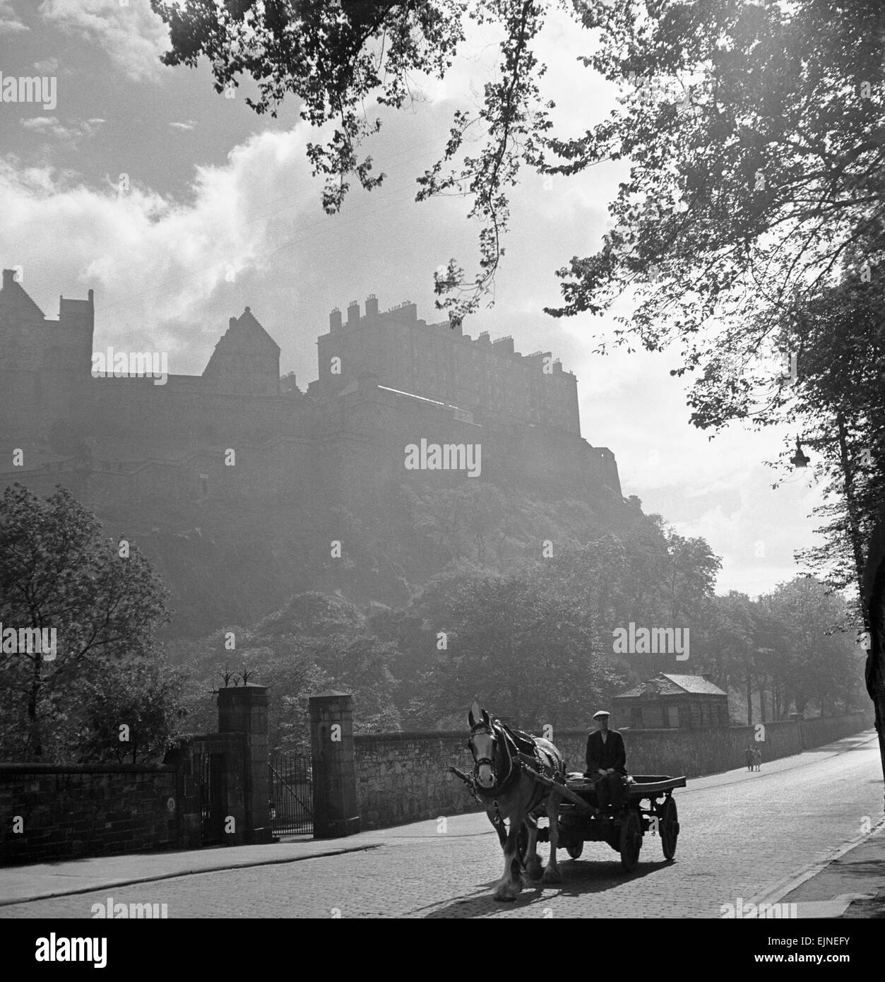 Horse and cart pass through peaceful countryside village Cobbled street Edinburgh Castle Scenery tranquil circa - Stock Image