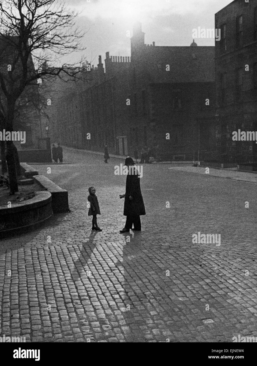 Edinburgh street scenes Policeman talking to lost child on a cobbled street in Edinburgh, Scotland. Scenic Atospheric - Stock Image