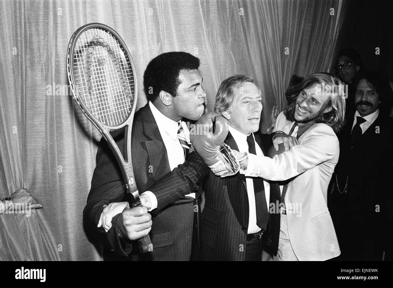 Singer Andy Williams breaks steps inbetween Heavyweight Boxing champion who is holding a tennis racket over Tennis - Stock Image