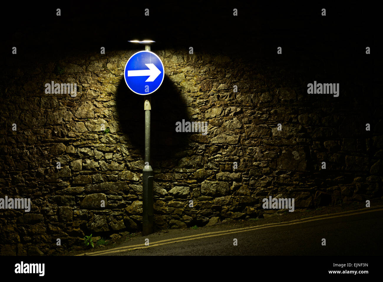 Road spot spotlit against a stone wall - Stock Image
