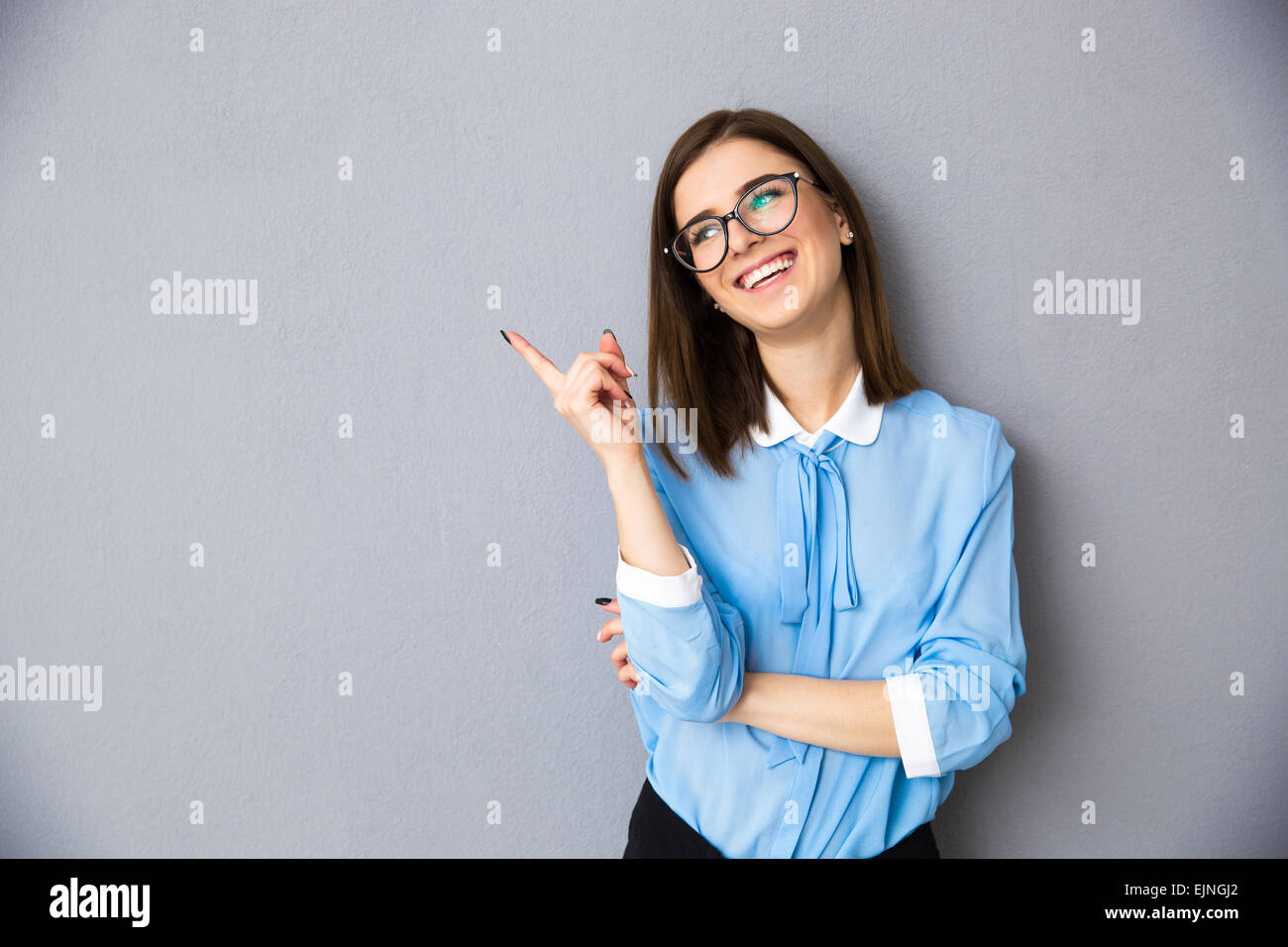 Cheerful businesswoman pointing away over gray background. Wearing in blue shirt and glasses. Looking away - Stock Image