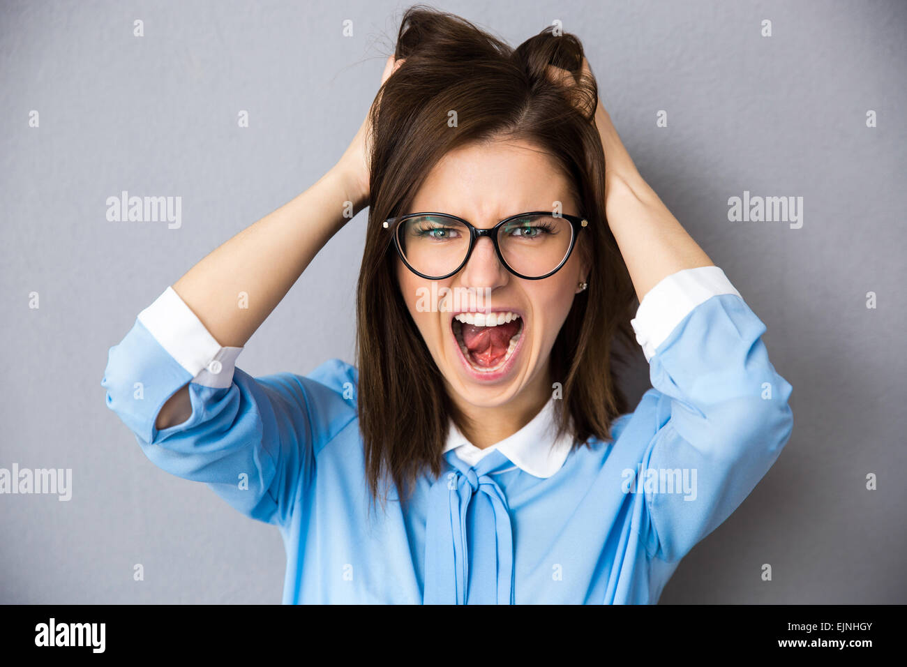 Angry businesswoman touching her hair and screaming over gray background. Wearing in blue shirt and glasses. Looking - Stock Image