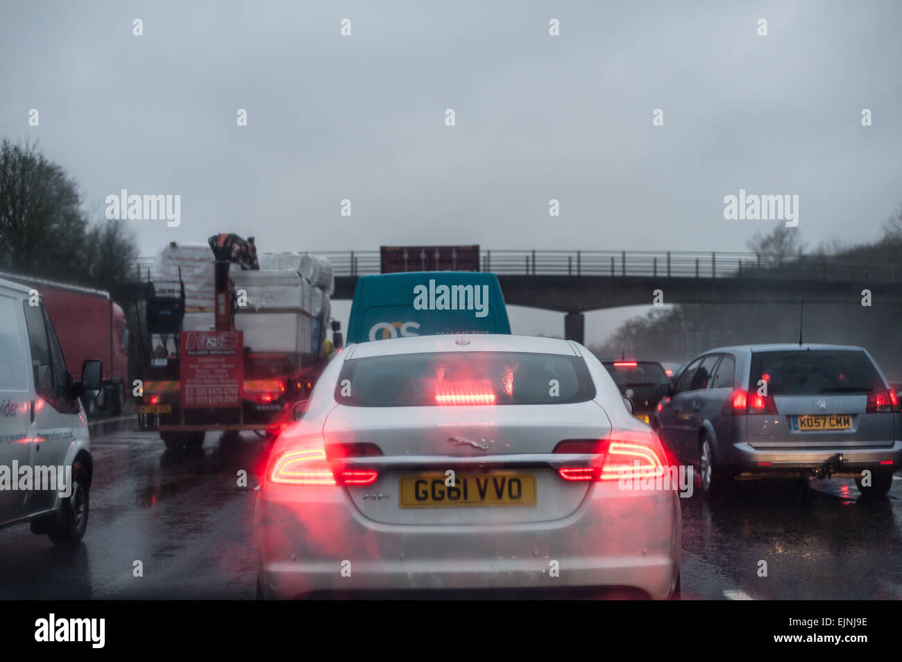 dreary wet rush hour journey standstill on motorway carriage stationary cars lorries with tail rear brake lights - Stock Image