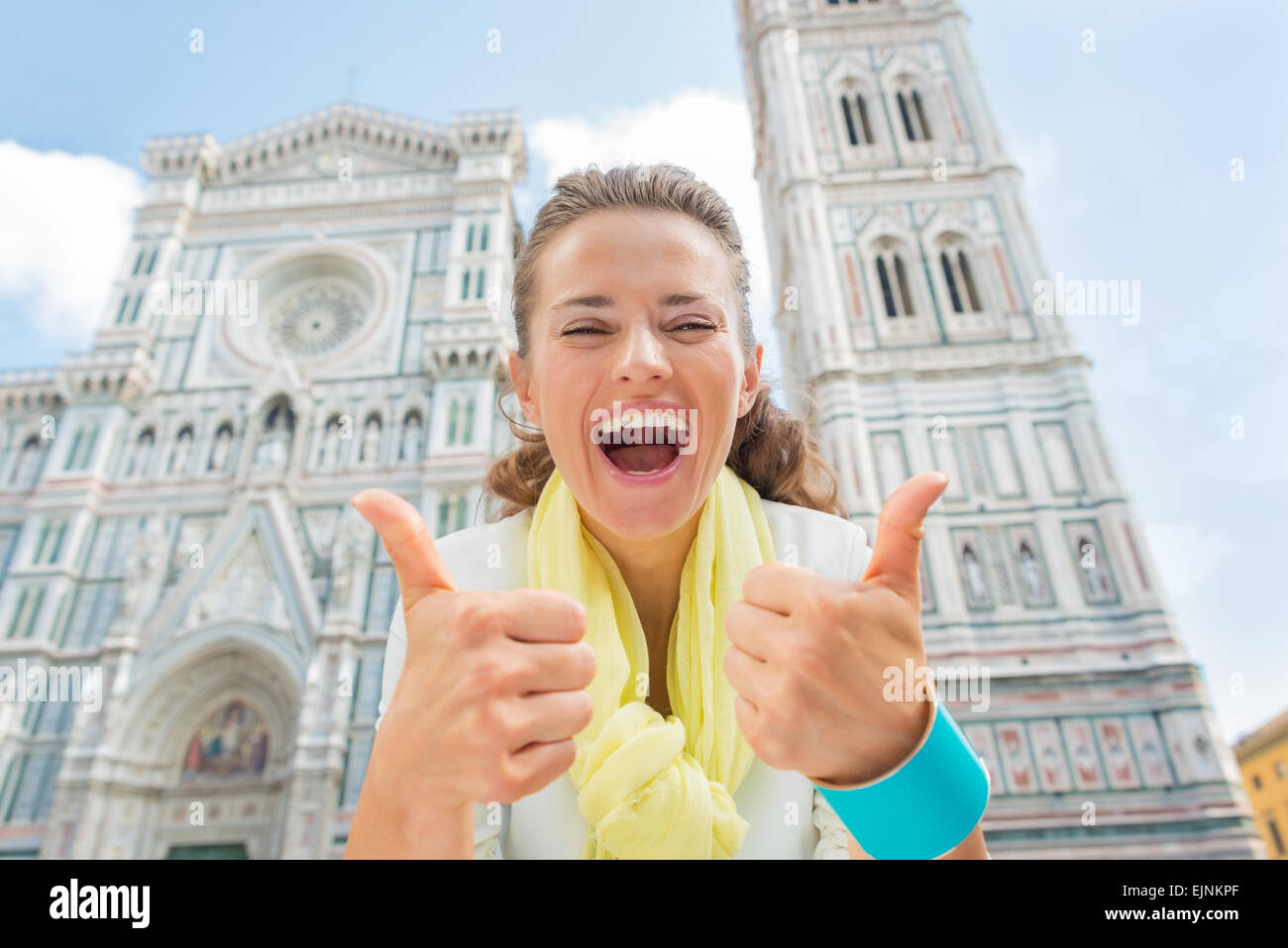 Happy young woman showing thumbs up in front of duomo in florence, italy Stock Photo