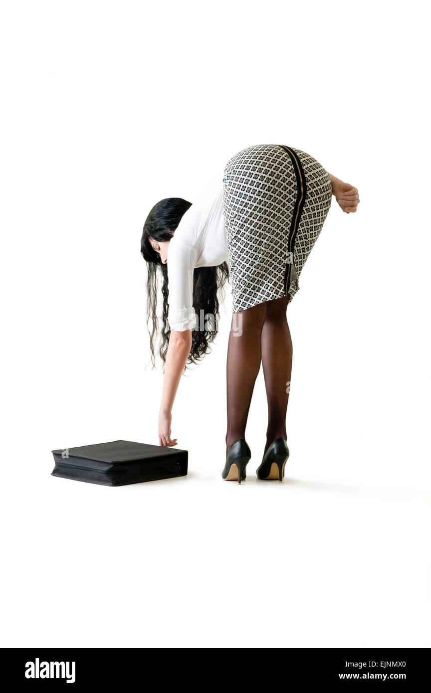 Young beautiful woman reaching down to pick up attache case - Stock Image
