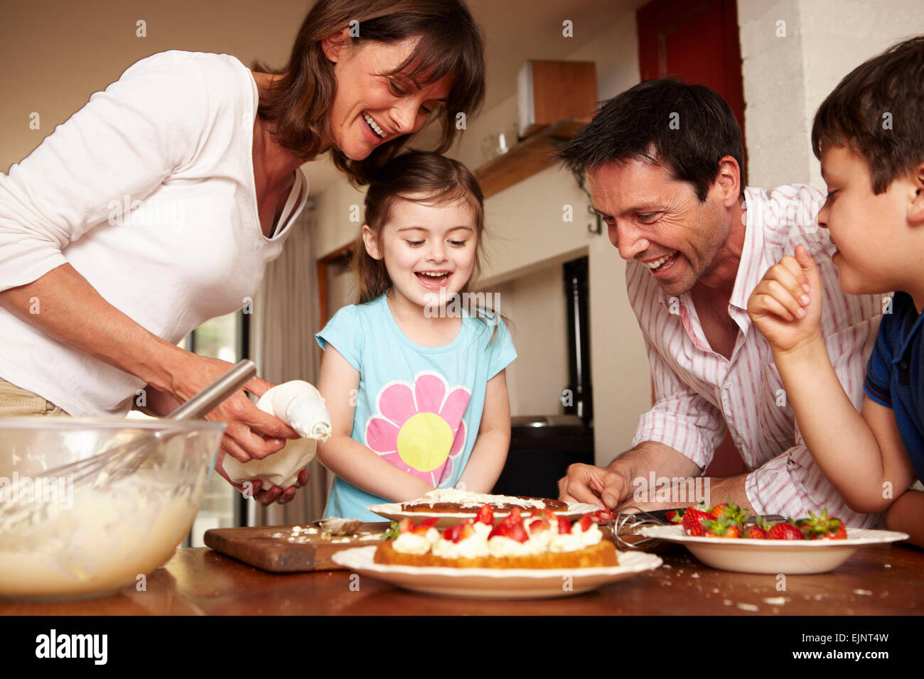 A family, two parents and two children in the kitchen icing a cake with fruit and cream. - Stock Image