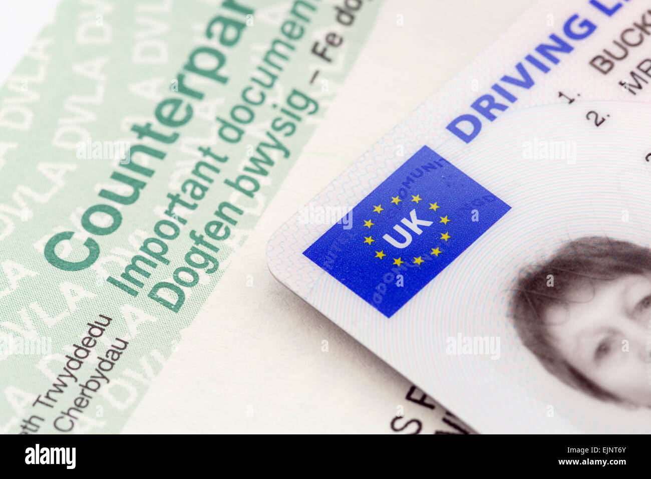 A UK plastic card photographic driving licence on a bilingual paper counterpart document in English and Welsh language - Stock Image