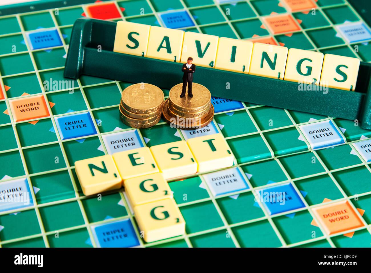 nest egg savings money saving pension investment investing words using scrabble tiles to illustrate spelling spell - Stock Image