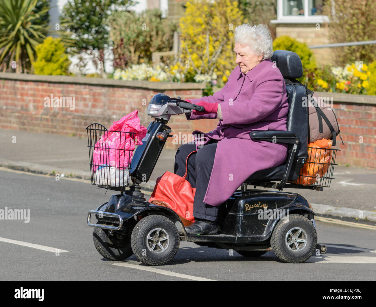 Mobility scooter. Elderly lady riding a mobility scooter across a road carrying shopping bags. - Stock Image