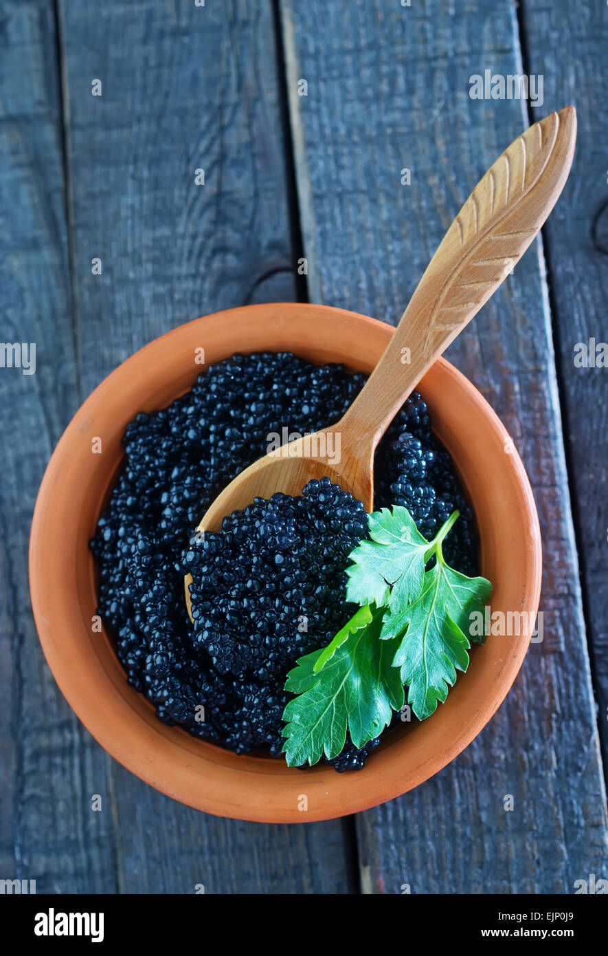 black caviar in bowl and on a table - Stock Image