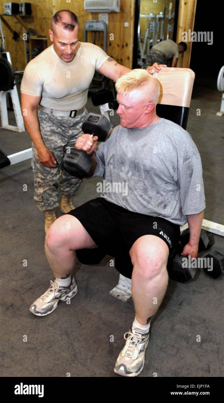 Sgt. 1st Class Luis R. Laluz supervises Sgt. Joshua S. Moak during a workout in a gym at Al Asad Air Base, Iraq, - Stock Image
