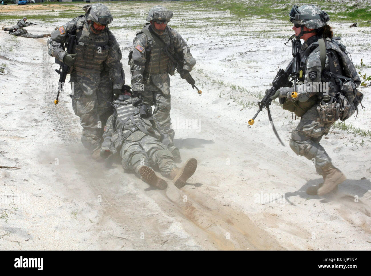 U.S. Army Soldiers drag Staff Sgt. Kevin Hartman out of harms way during an improvised explosive device training - Stock Image