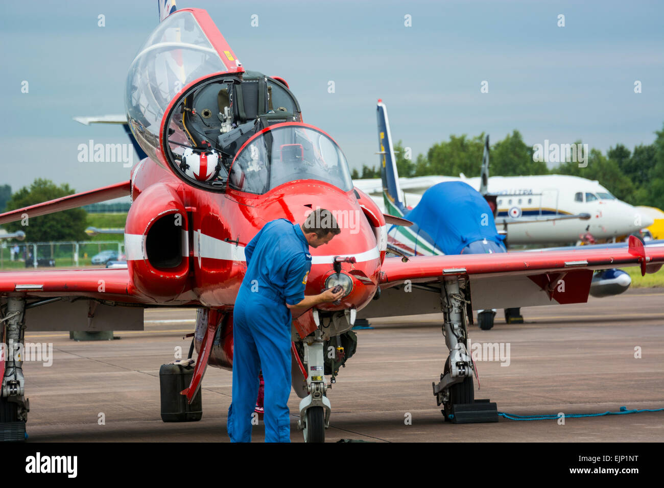 Red Arrows Hawk Aircraft being cleaned and prepared at RIAT 2014 by a member of the Blues - Stock Image