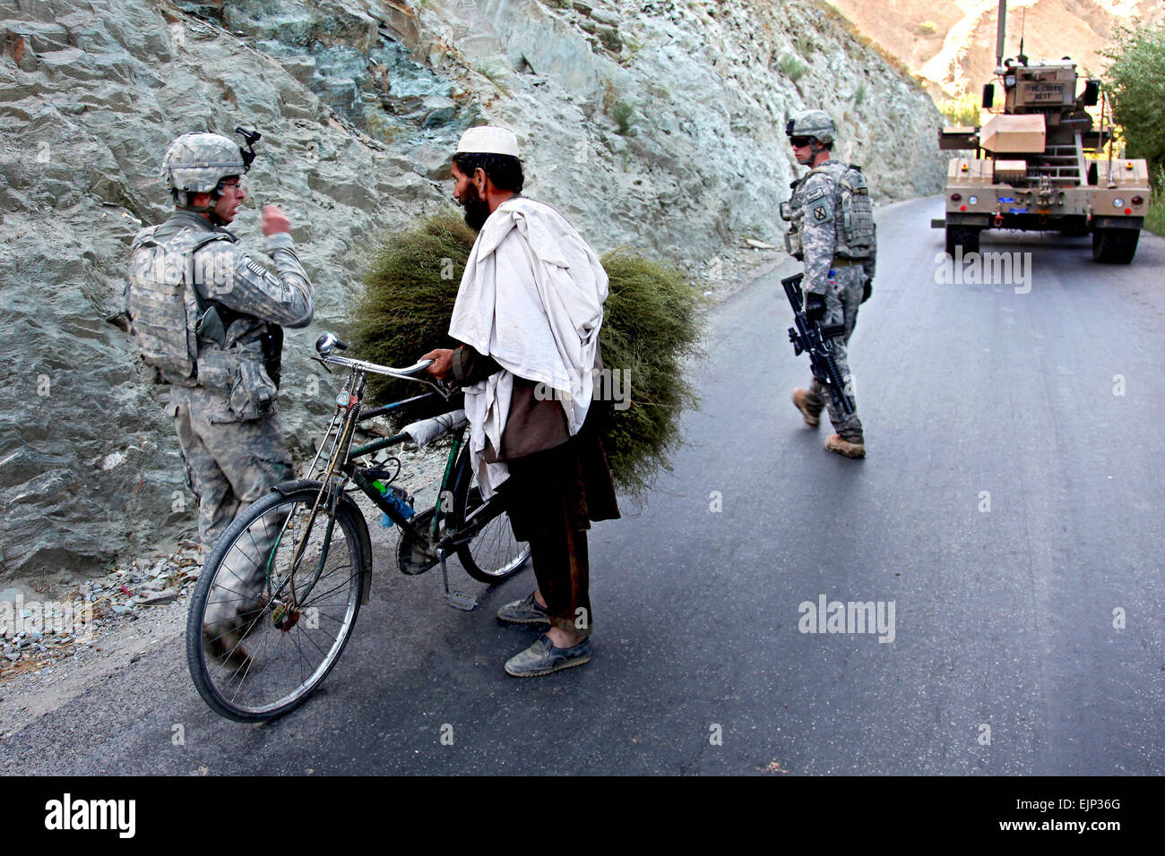 U.S. Army 1st Lt. Christopher George talks to an Afghan while patrolling the streets in Wardak province's Tangi - Stock Image
