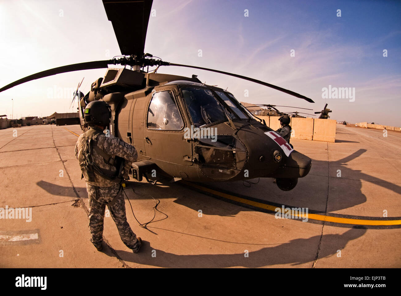 Army helicopter crew chiefs of C Company, 3rd Battalion, 126th Aviation Regiment, stand outside an HH-60M MEDEVAC - Stock Image