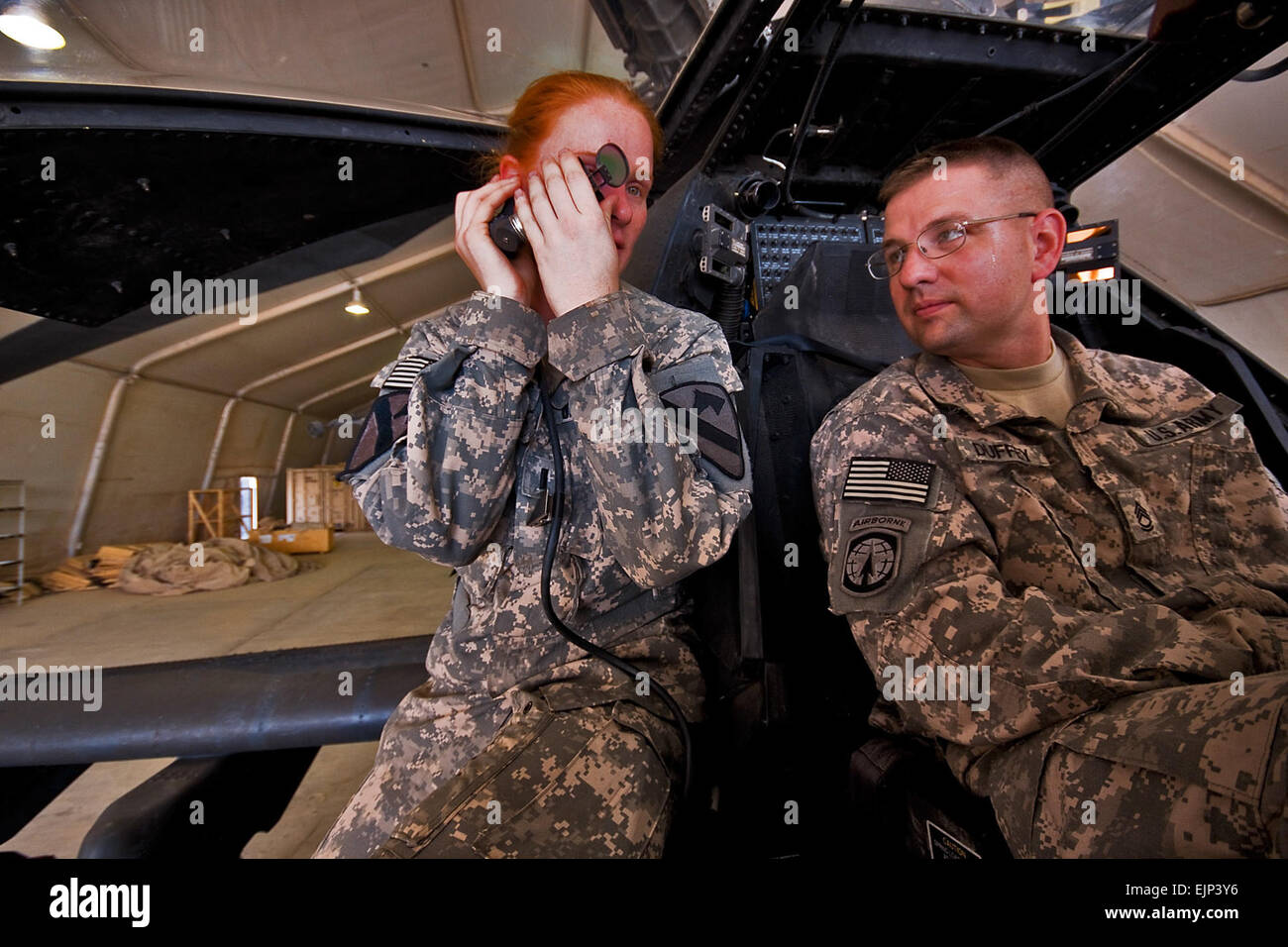 Camp Taji, Iraq, Aug 10, 2009- While going through various components of an AH-64D Apache attack helicopter, 1st Lt. Carolyn Wagnild left, from Boise, Idaho, an Apache pilot in Company C, 1st Battalion, 227th Aviation Regiment, 1st Air Cavalry Brigade, 1st Cavalry Division, explains how the sighting system of the Apache works to Sgt.1st Class Jonathan Duffey, from Troy, Ohio, the tactical operations center noncommissioned officer in charge for 2nd Battalion, 107th Cavalry Regiment of the Ohio National Guard. The meeting between the two units is meant to build trust and understanding between th Stock Photo