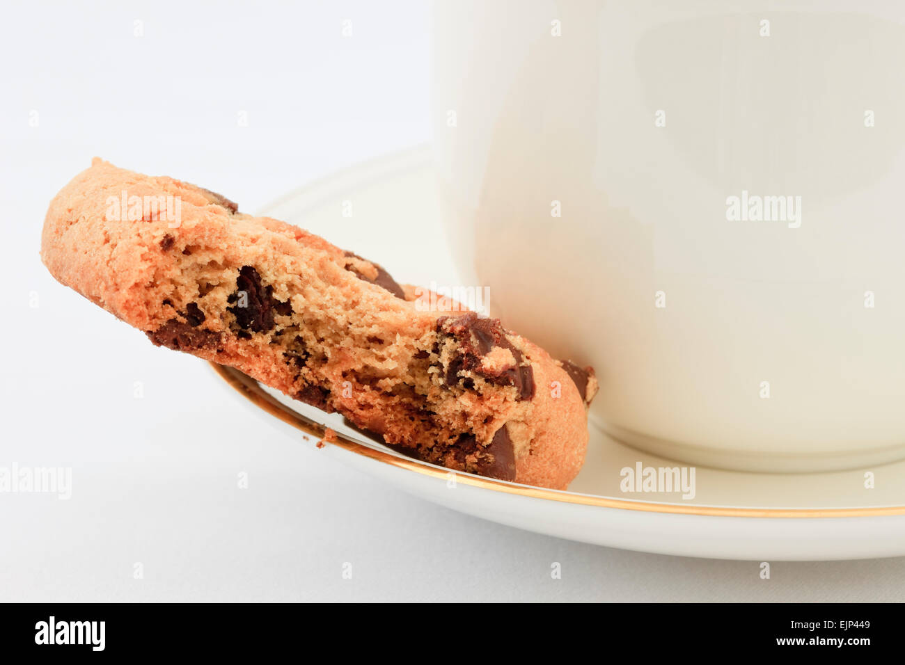 Chocolate chip biscuit with a bite taken out on the saucer with a cup of English tea. England, UK, Britain - Stock Image