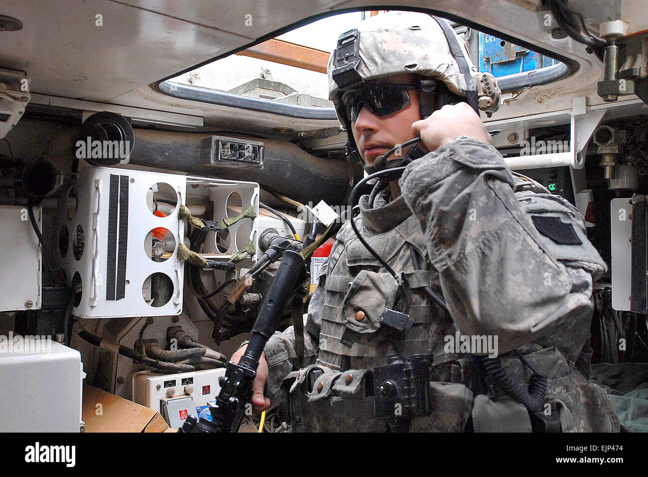 U.S. Army Staff Sgt. Bert Finland checks his headset radio in a   Stryker vehicle before patrolling in Taji, north - Stock Image