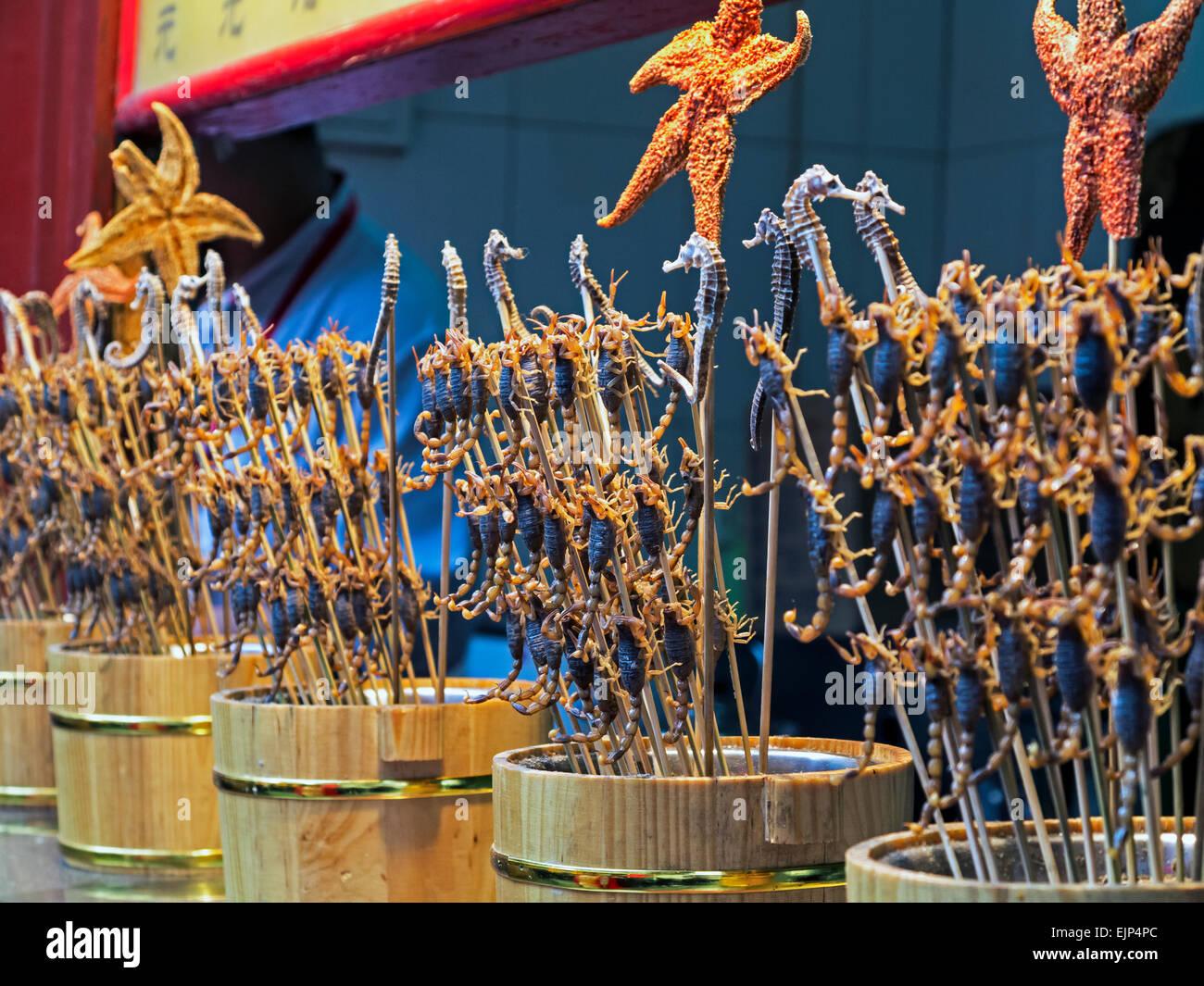 China, Beijing, scorpions and starfish on skewers, Wangfujing street night market - Stock Image