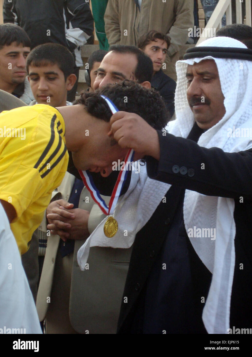 A medal is presented by a local leader to a player from the Hammamiat Soccer Club at the Taji Soccer Club Stadium, - Stock Image