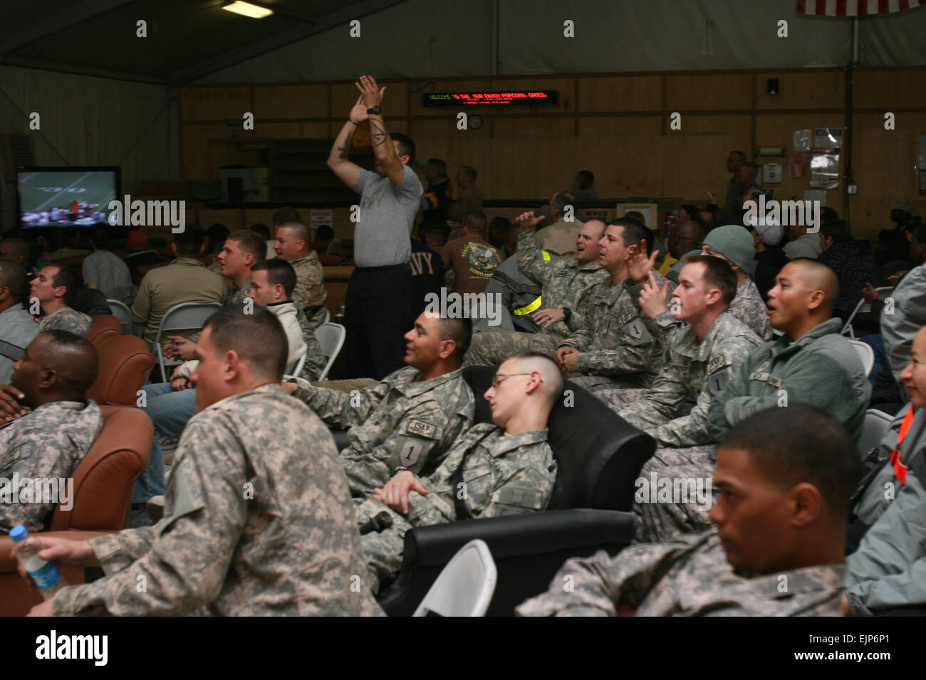 KANDAHAR AIRFIELD, Islamic Republic of Afghanistan – Deployed service members cheer for their favorite teams while - Stock Image