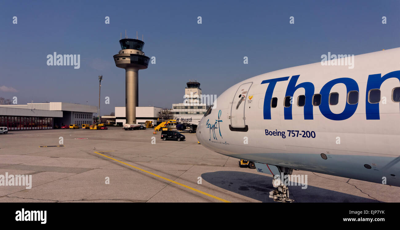Salzburg Airport control tower with Thomas Cook aircraft in foreground. - Stock Image