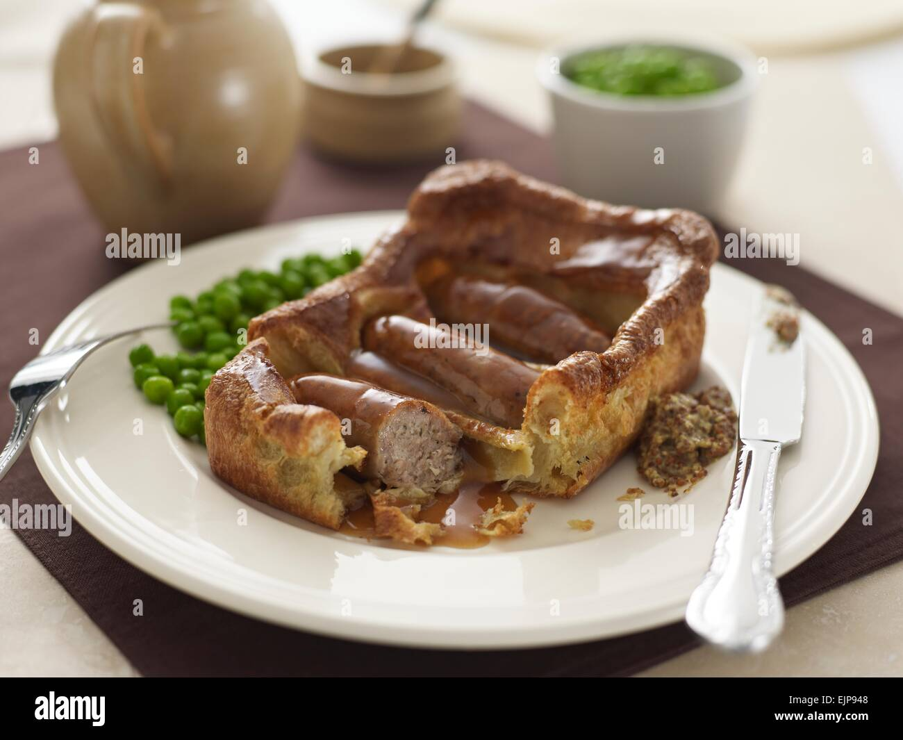 plated Meal of Toad in the hole large square Yorkshire pudding with three sausages gravy peas and whole grain mustard - Stock Image