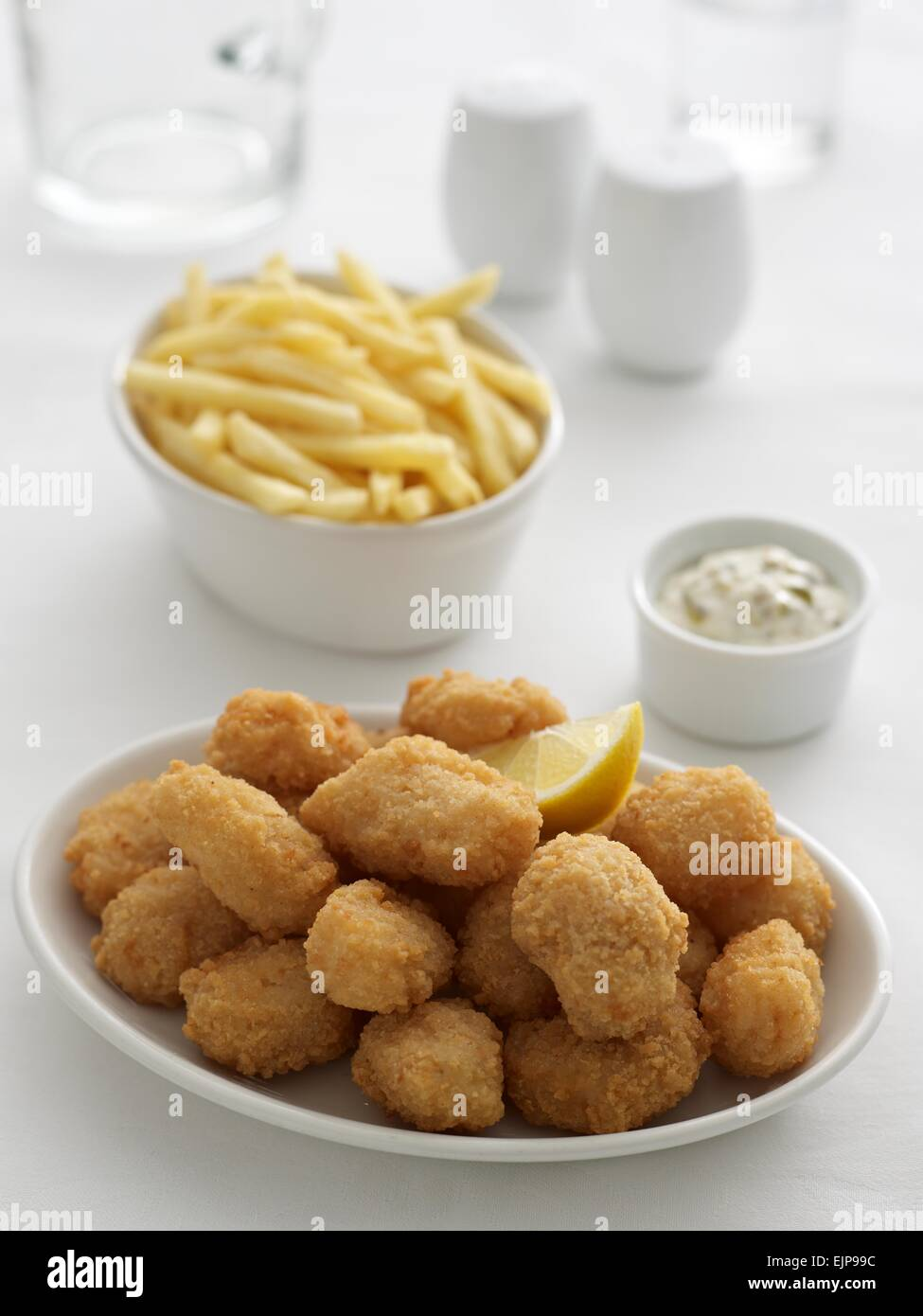 Breaded fish nuggets chips and peas in separate bowls tartare sauce cruet set jug and glass of water. - Stock Image