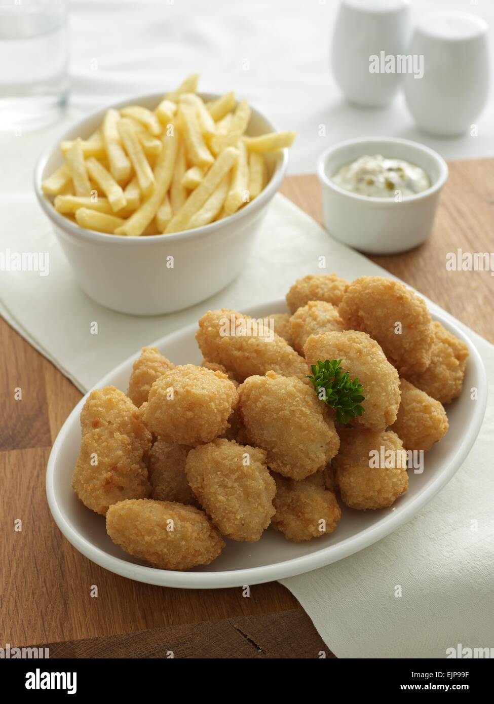 Breaded fish nuggets chips  separate bowls tartare sauce cruet set glass of water.wooden board - Stock Image