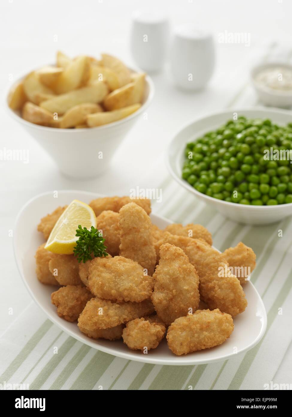 breaded fish goujons, lemon and parsley in a bowl plus bowls of skin on chips,rustic style, garden peas, ramekin - Stock Image